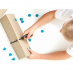 photo of kid cutting cardboard